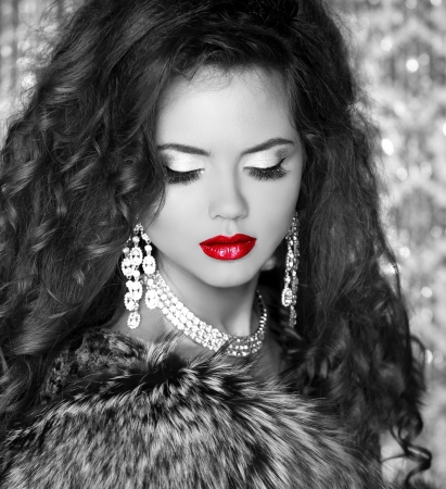 fashion jewelry: Red lips, Beautiful Woman in Luxury Fur Coat. Black and white photo Stock Photo