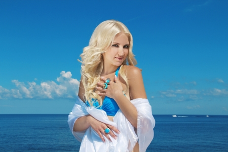 Portrait of beautiful blond woman on blue sky background photo