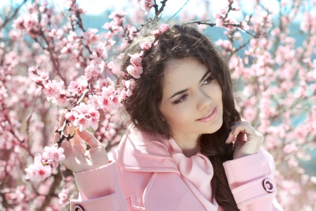 Beautiful young woman over pink blossom tree, outdoors portrait photo
