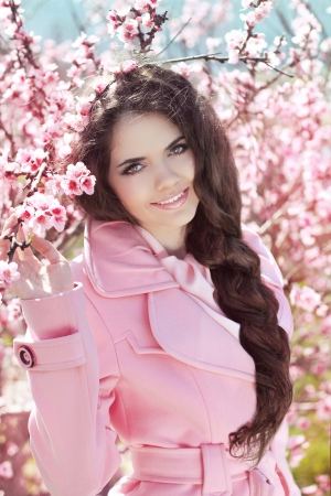 braided hair: Beautiful brunette girl with braided hair over pink blossom tree, outdoors portrait