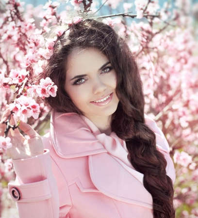 Beautiful smiling girl over pink blossom tree, outdoors portrait photo