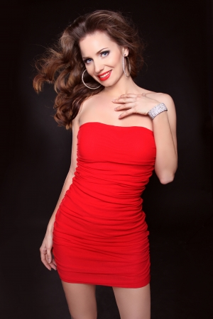 Beautiful smiling woman in red dress posing isolated on black background, studio shot  photo