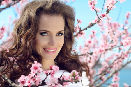 Outdoors portrait of beautiful smiling woman model in pink blossoms on spring day photo