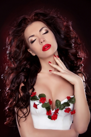strand of hair: Hot Red Lips. Portrait of sexy brunette girl with professional make-up and hairstyle over dark background Stock Photo