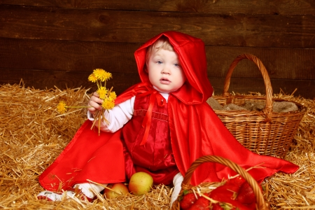 hayloft: Cute little girl with dandelions wearing in red clothing resting on pile of straw