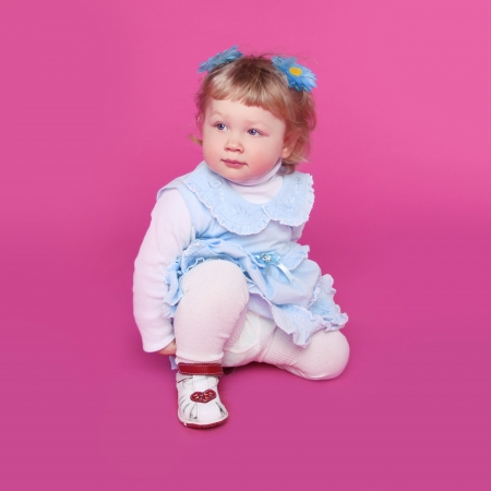 Portrait of funny cute little girl over pink background photo