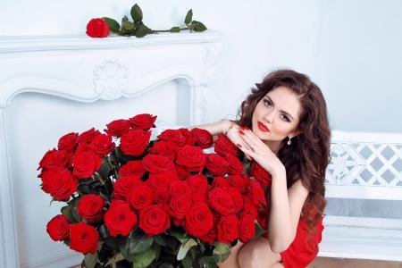 sexualidad: Hermosa mujer morena con rosas rojas ramo de flores en el moderno apartamento interior