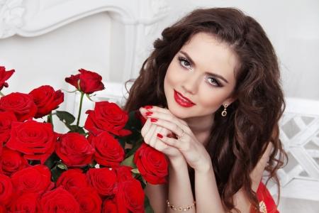 mujer con rosas: Atractiva chica sonriente con el ramo de rosas rojas en el interior moderno