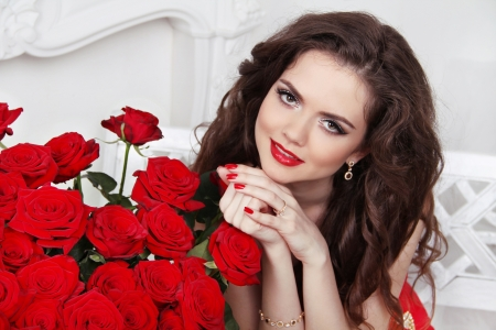 Attractive smiling girl with bouquet of red roses at modern interior Stock Photo