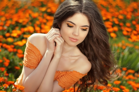 Young woman outdoors portrait over orange marigold flowers Zdjęcie Seryjne