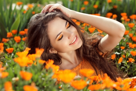 a tooth are beautiful: Enjoyment - free smiling woman enjoying happiness. Beautiful woman embracing in golden marigold flowers Stock Photo