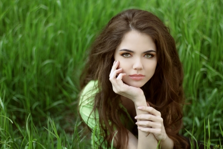 teen girl brown hair: Young brunette woman on the green field grass, outdoors portrait  Stock Photo