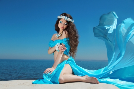 Beautiful woman model in Blowing Dress Flying resting over blue sky photo