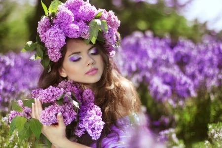 Beautiful young woman in lilac flowers, outdoors portrait photo