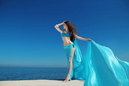 Enjoyment - free sexy woman enjoying happiness. Beautiful woman in blue chiffon dress embracing with tissue over blue sky photo