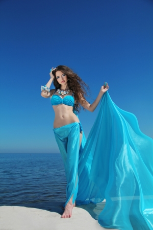 Enjoyment - free sexy woman enjoying happiness. Beautiful woman in blue chiffon dress embracing over blue sky photo