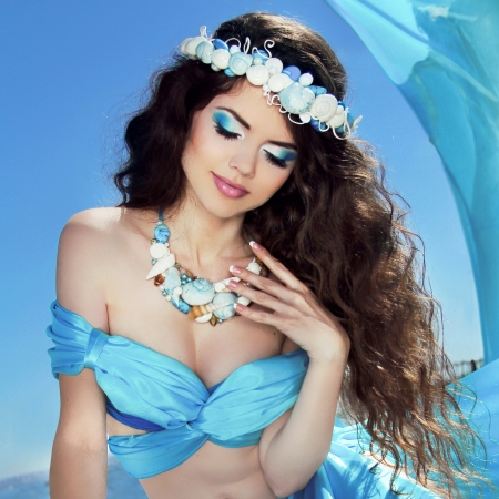 Makeup. Sea jewelry. Long Healthy Hair. Beautiful girl in blue silk luxury dress relaxing over blue sky