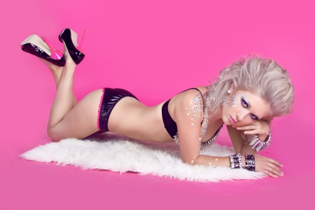 beautiful bdsm: Beautiful woman with hair styling lying over pink background. Sexy girl in lingerie. Fashion art photo