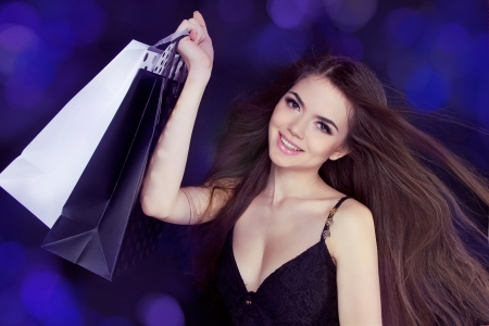 Happy Smiling beautiful girl with shopping bags at copy space. photo