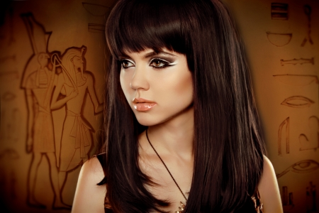 hieroglyphs: Hair. Beautiful Brunette Girl over Egyptian hieroglyphs