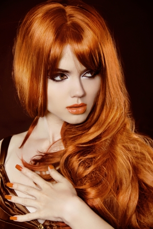 Beautiful woman with red curly hair and evening make-up over black photo