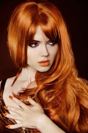 unas largas: Mujer hermosa con el pelo rojo rizado y maquillaje de la tarde sobre el negro