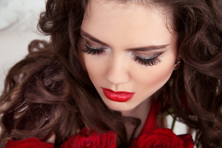Closeup portrait of beautiful woman with curly hair and fashion makeup with red roses  Eyelashes  Eye shadows  photo