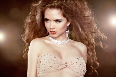 Beauty Glamour Portrait of sexy woman with long curly hair and fashion makeup over party lights. photo