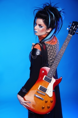 Back of Rock emo girl posing with electric guitar isolated on blue background photo