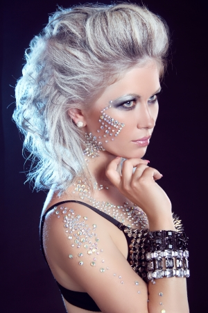 studs: Hairstyle  Fashion Beauty Girl  Punk Style Woman with strasses on face, on a dark background Stock Photo