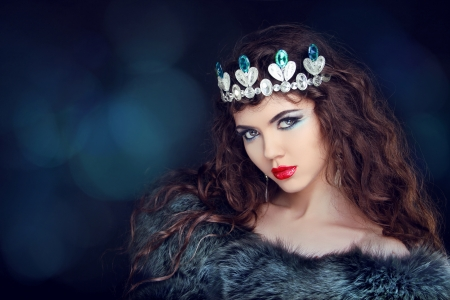 queens: Beautiful woman luxury portrait with long hair in fur coat. Jewelry and Beauty. Fashion art photo Stock Photo