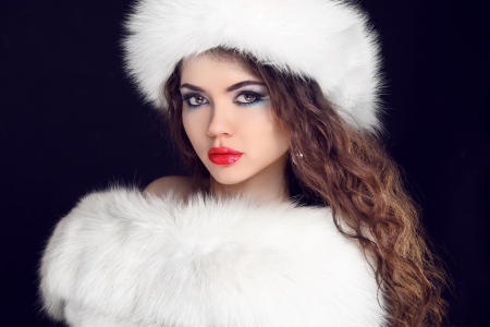 Beautiful Girl wearing in White Fur Coat and Furry Hat. Winter Woman Portrait over Black 스톡 콘텐츠