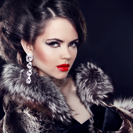 Jewelry and Fashion elegant lady. Beautiful Woman wearing in Luxury Fur Coat over black background.