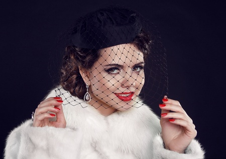 Retro lady with hat. Beautiful Woman in Luxury Fur Coat.  Fashion model Isolated on dark background. photo