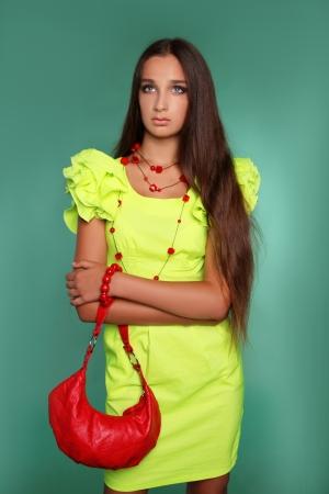 dishevel: Bella giovane donna con lunghi capelli castani. Bella modello pone in abito stile di moda in studio.