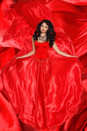 Beautiful brunette woman wearing in magnificent red dress on fabric texture background photo