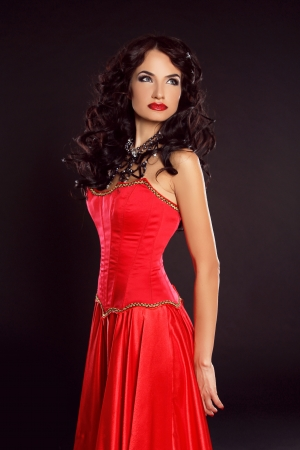 Beautiful woman in red dress isolated on black background. Luxury Style. Fashion Photo. photo