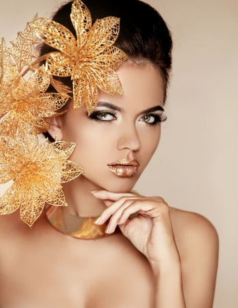 Beautiful Girl With Golden Flowers. Beauty Model Woman Face. Perfect Skin. Professional Make-up. Makeup. Fashion Art Photo. 스톡 콘텐츠