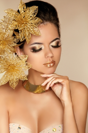Beautiful Girl With Golden Flowers. Beauty Model Woman Face. Perfect Skin. Professional Make-up. Makeup. Fashion Art photo