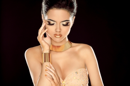 Fashion photo of beautiful brunette woman posing in golden jewelry isolated on black background