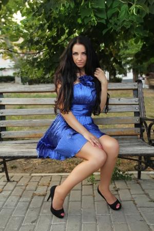 long weekend: Beautiful brunette woman wearing in blue dress resting on bench over park. Outdoors Portrait.