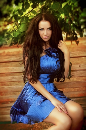 Beautiful brunette woman wearing in blue dress resting on bench over park. Outdoors Portrait. photo