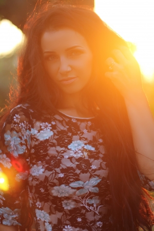 outspread: Enjoyment, free happy woman enjoying sunset. Beautiful brunette girl model embracing the golden sunshine glow of sunset with arms outspread and face raised in sky enjoying peace. Outdoors Portrait