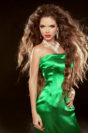 Fashion Beauty Girl with long brown blowing hair posing in elegant dress isolated on black background photo
