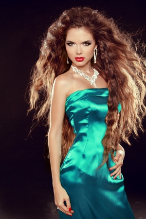 Beautiful elegant woman with long curly hairs in elegant dress posing in studio. photo
