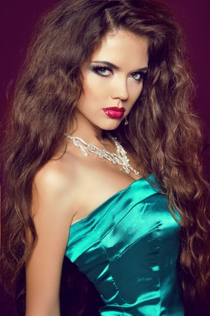 Beautiful woman with curly hair and evening make-up. Jewelry and Beauty. Fashion studio photo photo