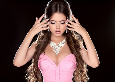 Beauty Woman. Fashion Model Girl with Long Brown Hair showing jewelry in pink dress  isolated on black background. Manicured nails. Stock Photo