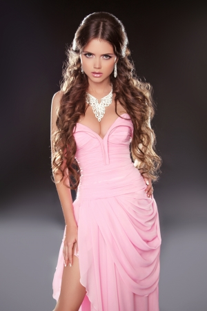 Beautiful brunette woman posing in pink gorgeous dress isolated on dark background