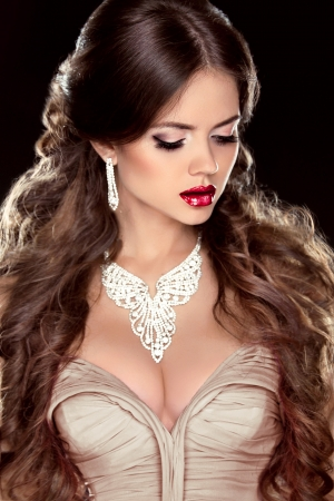 red lips: Brown Hair. Fashion girl model. Beautiful woman with brown wavy long hair. Jewelry. Hot Lips. Stock Photo