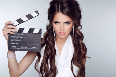 Beautiful brunette woman holding Clapper Board against a grey background photo
